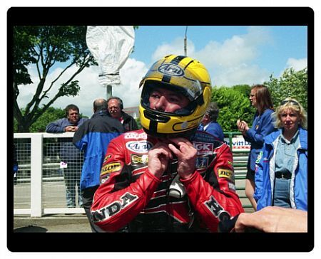 Joey Dunlop unclips his trade mark Yellow Arai helmet for the last time in the Isle of Man. Winner of three races in 2000, he finished third in the Senior TT. No one has eclipsed his 26 TT victories from 100 races round the TT course