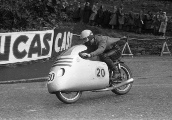 With his overjacket flapping in the breeze, Italian Carlo Ubbiali heads for his second of five TT wins. The Clypse Course did not take in the Governors Bridge dip