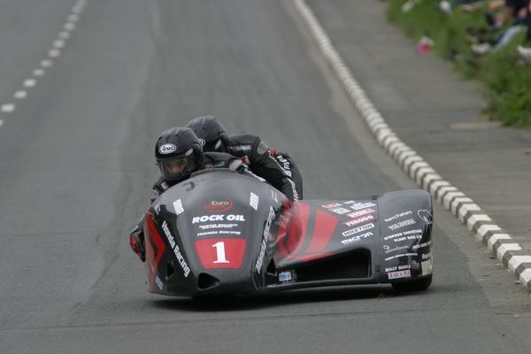 Four lean years came to an end when Dave Molyneux won the 2003 Sidecar race B. Seen here at Sulby Bridge with Craig Hallam keeping the rear wheel down