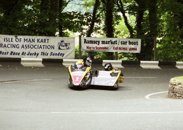 Swinging the DMR Honda through Ramsey Hairpin, Dave Molyneux and new passenger Dan Sayle took their first TT win together in the 2004 Sidecar race A. They made it a double with a victory in Race B that year