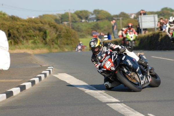 With flames spurting from the tailpipe of his TAS Suzuki, Guy Martin heels in Ballakeighan at the 2011 Southern 100