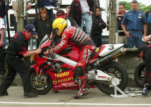 Davy Wood steadies the bike as Irish ace Joey Dunlop brings his Honda SP1 in for a pit stop. Joey went on to win the 24th of his 26 TT victories