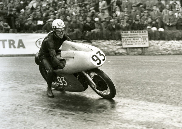 Ray Amm drops a precautionary foot as he slithers through Quarter Bridge as he wins the 1954 Senior TT
